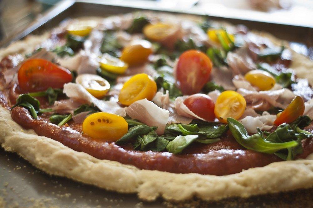 close up of thin and crispy  gluten free pizza with tomato, prosciutto, spinach and tomato sauce