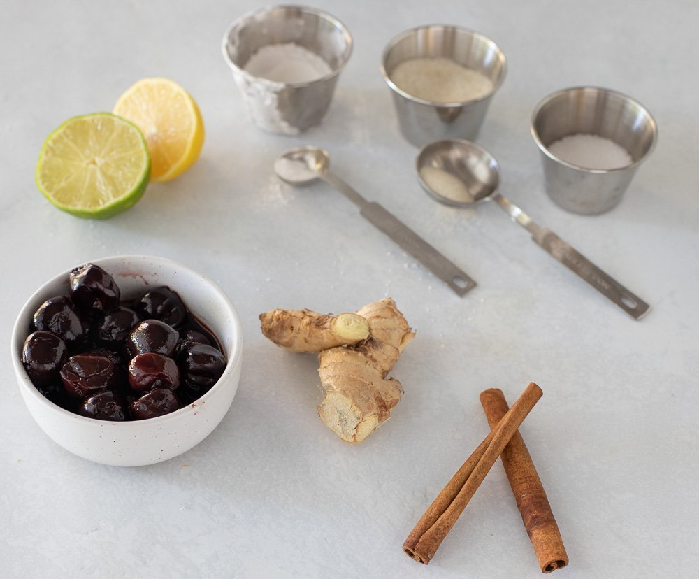 fruit compote ingredients - bowl of thawed frozen cherries. fresh ginger, halves of lemon and lime, cinnamon sticks and small metal cups and measuring spoons with tapioca starch, sugar and salt