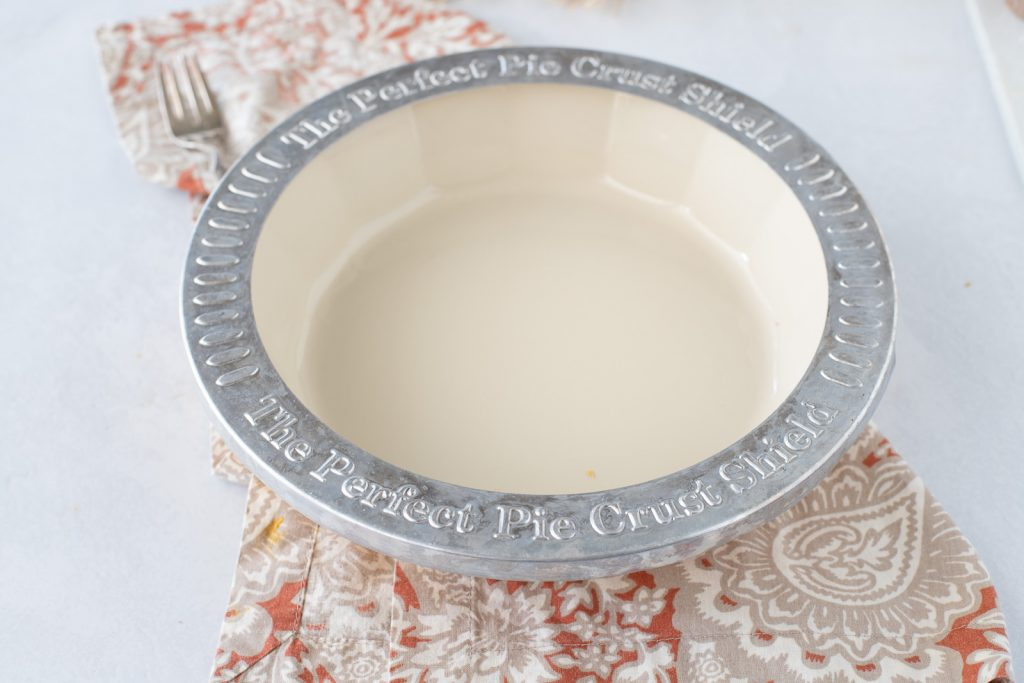 overhead view of ceramic pie dish with metal pie crust shield