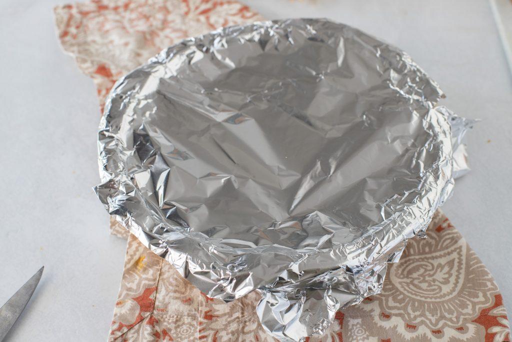 tin foil on top of pie dish on top of paisley print napkin.