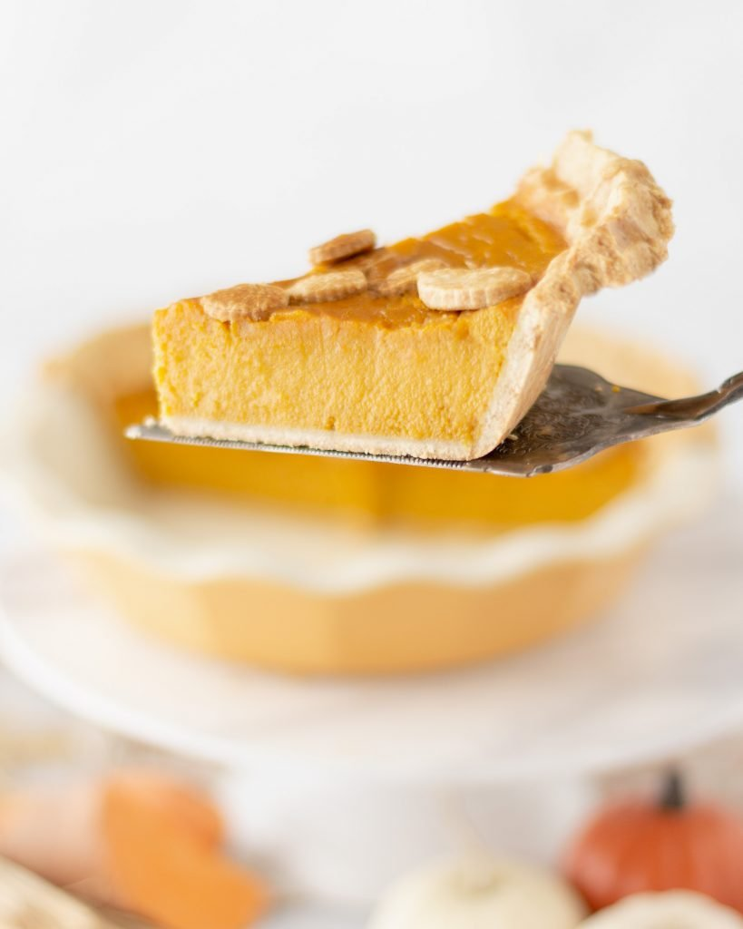 close up of slice of sweet potato pumpkin pie on pie server with pie plate in back ground