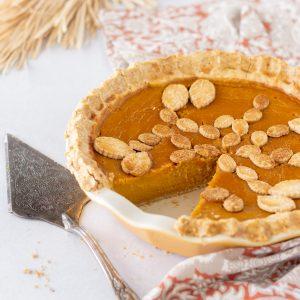close up of gluten free sweet potato pumpkin pie in ceramic pie dish with 1 slice removed. Pie server on left.