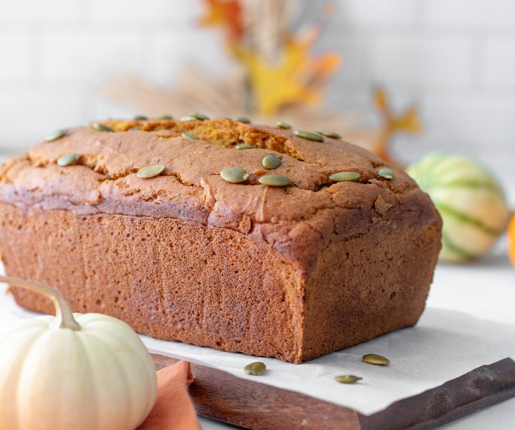 close up of loaf of gluten free vegan pumpkin bread on wood tray and white parchment with white pumpkin, autumn leaves, cinnamon sticks and orange napkin in front