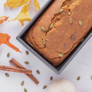 overhead view of gluten free vegan pumpkin bread in loaf pan withautumn leaves, cinnamon sticks and pumpkin seeds