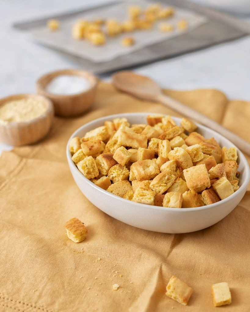 Gluten-Free cornbread cubes in white bowl on yello napkin. Wood spoon and bowls with salt & cornmeal in background.