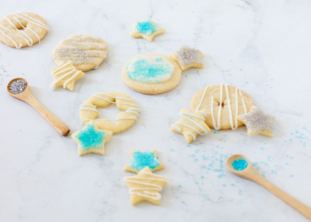 gluten free cut out cookies - round and star shaped with white icing, turquoise and silver sugar on white marble background, small wood spoons with sanding sugar
