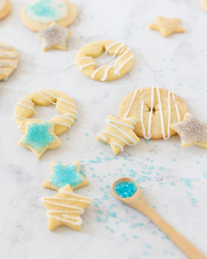 gluten free cut out cookies - round and star shaped with white icing, turquoise and silver sugar on white marble background