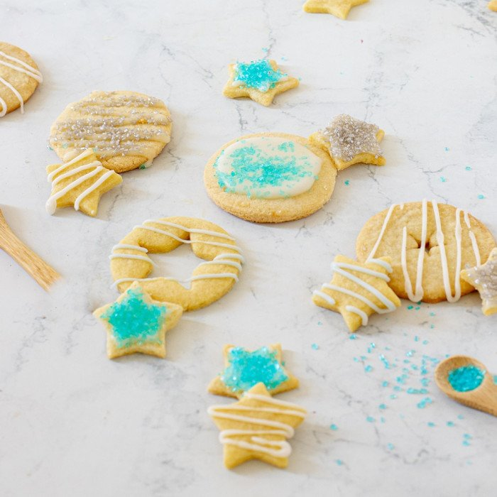 no spread gluten free cut out cookies in star and round shapes with white icing and turquoise sanding sugar on white background