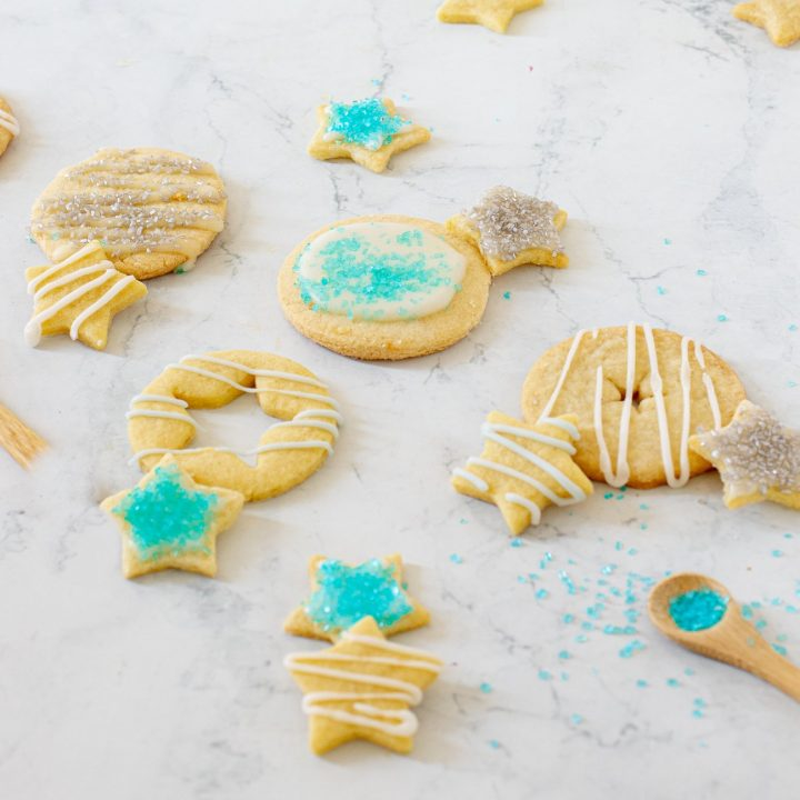 no spread, gluten free cut out cookies with icing and turquoise sanding sugar. Round and star shapes. Small wood spoon with sugar in lower right. white marble background
