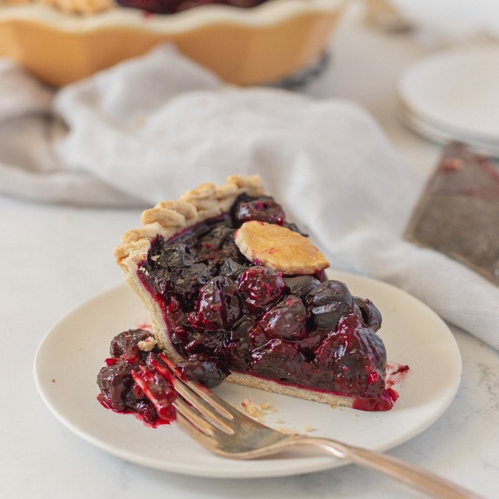 close up of slice of gluten free cherry pie on white plate with fork. Pie server on right and whole pie in background.