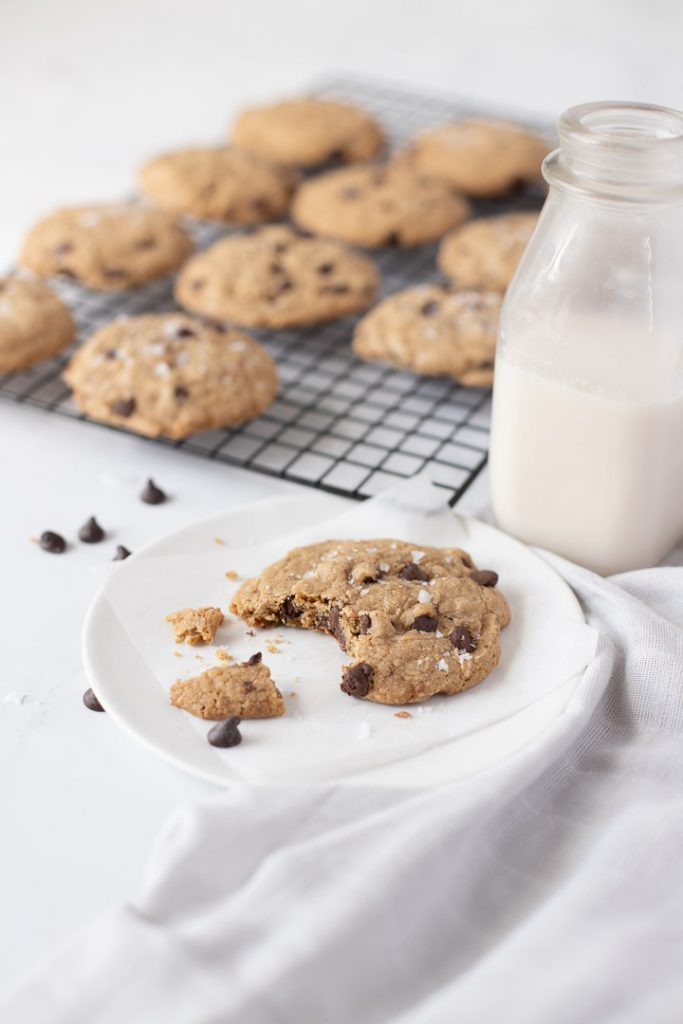 White plate with bitten cookie with milk bottle behind. WIre rack with cookies in back on white background.