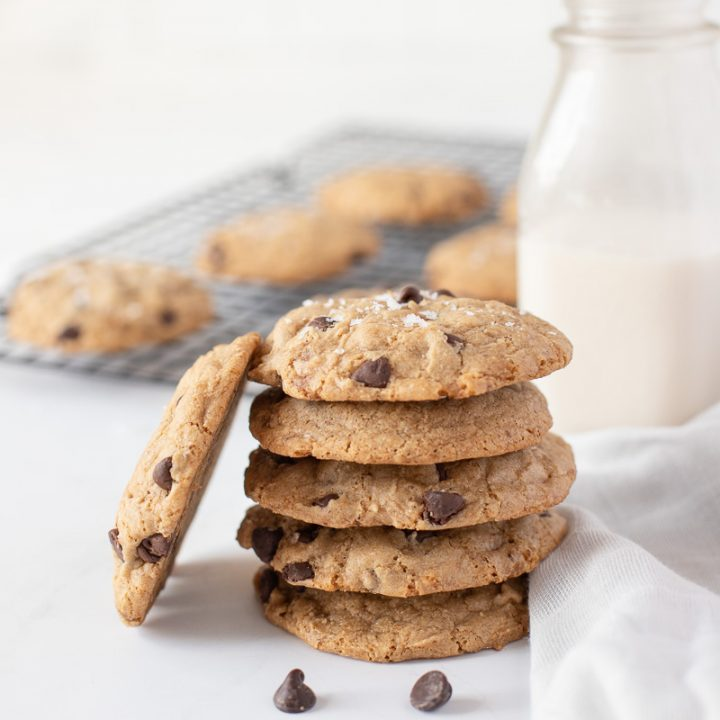stack of vegan gluten free chocolate chip cookies with milk bottle and cooling rack in back