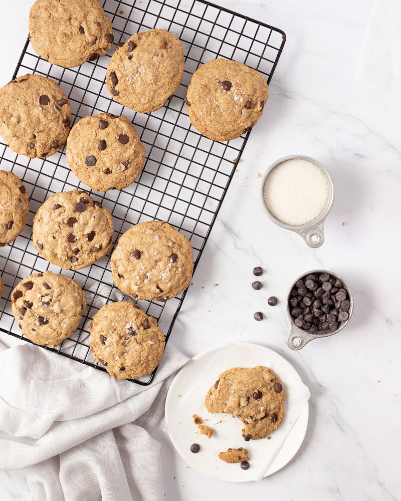 overhead view of vegan gluten free chocolate chip cookies on wire rack. White plate with bitten cookie in lower right. Measuring cups with sugar and chocolate chips on right.