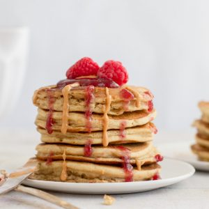 white plate with stack of 5 gluten free pancakes with peanut butter and raspberry jam dripping down, topped with raspberries. knife and raspberry cover spoon in front, white bowl in background left and stack of pancakes in back right,