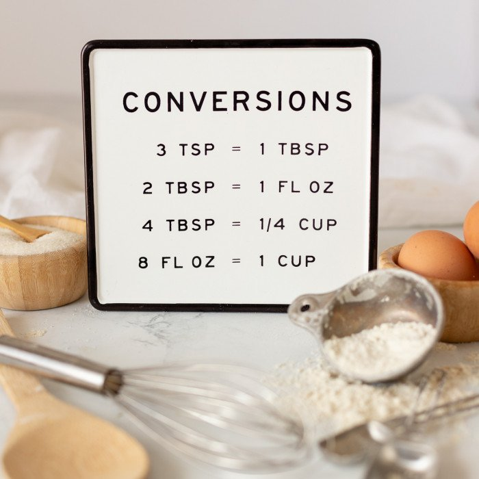 baking conversions sign with baking tools, measuring cup with flour and wood bowl with eggs