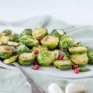 Roasted brussels sprouts piled on white platter garnished with pomegranate seeds. Serving spoon in front left. Gray background.