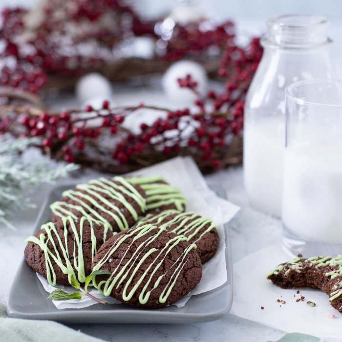 gluten free chocolate mint cookies with green icing on gray plate with cranberry wreath in back, milk glass, milk bottle and bitten cookie on right