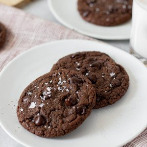 2 chocolate chocolate chip cookies topped with coarse salt on white plate. Plate with cookie in back, milk bottle on right.