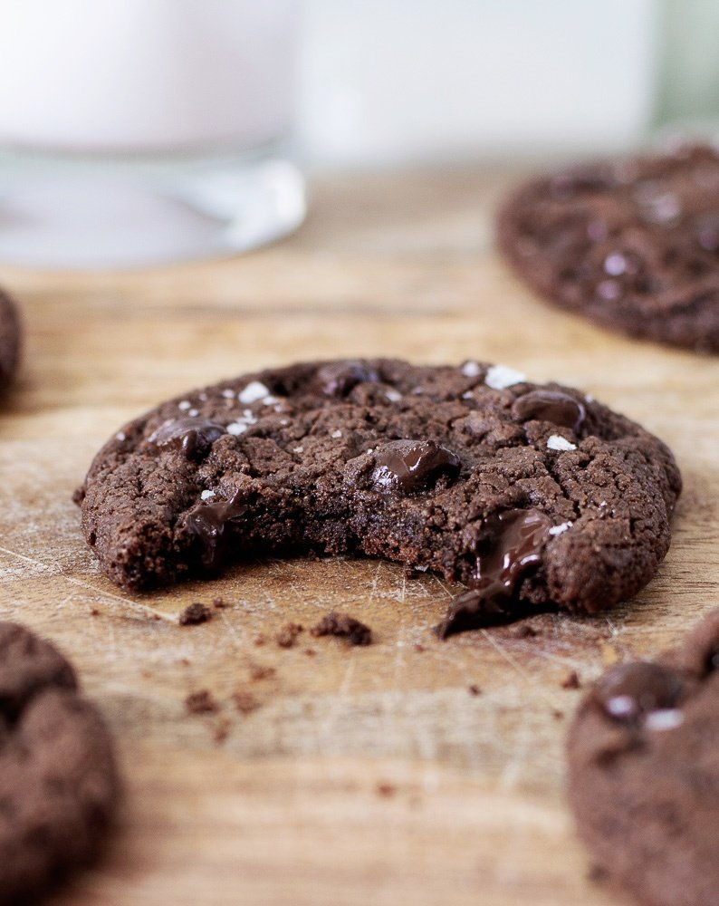 Close up of gluten-free chocolate chocolate chip cookie with bir taken out & melting chips.