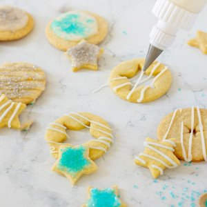 squeeze bottle drizzling easy cookie icing onto gltuen free cut out cookie. Decorated cookies with icing and sugar.