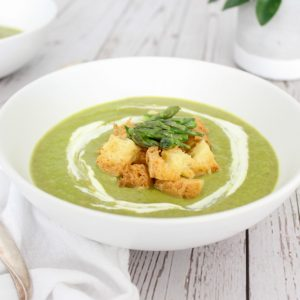 white bowl with asparagus soup garnished with croutons and asparagus tip with swirl of cream.