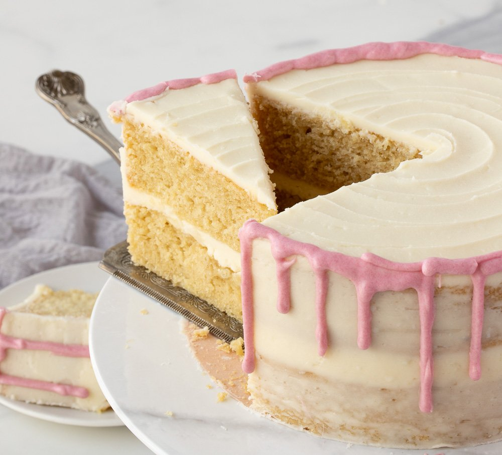 2 layer gluten free vanilla cake with buttercream frosting and pink drizzle on white marble cake stand. Cake server pulling slice from cake. Plate with slice of cake in back left. White background.