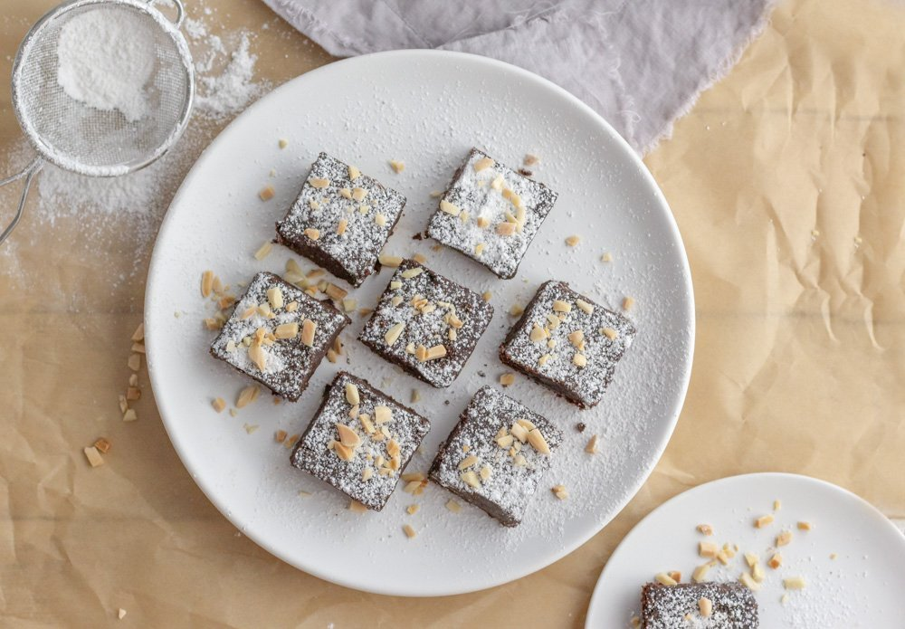 overhead view of gluten free fudge brownies dusted with powdered  sugar, topped with slivered almonds on round white plate. Brown parchment and gray napkin, with sugar sieve in upper left
