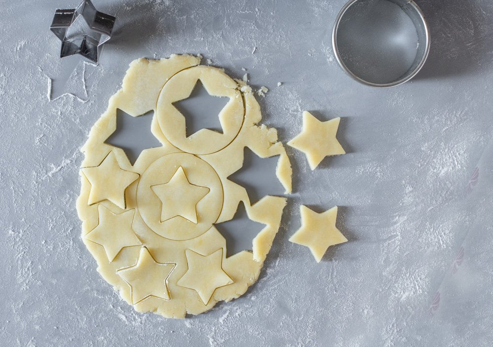 overhead view rolled no spread gluten free cut out cookie dough on gray mat. Stars and circles cut out.