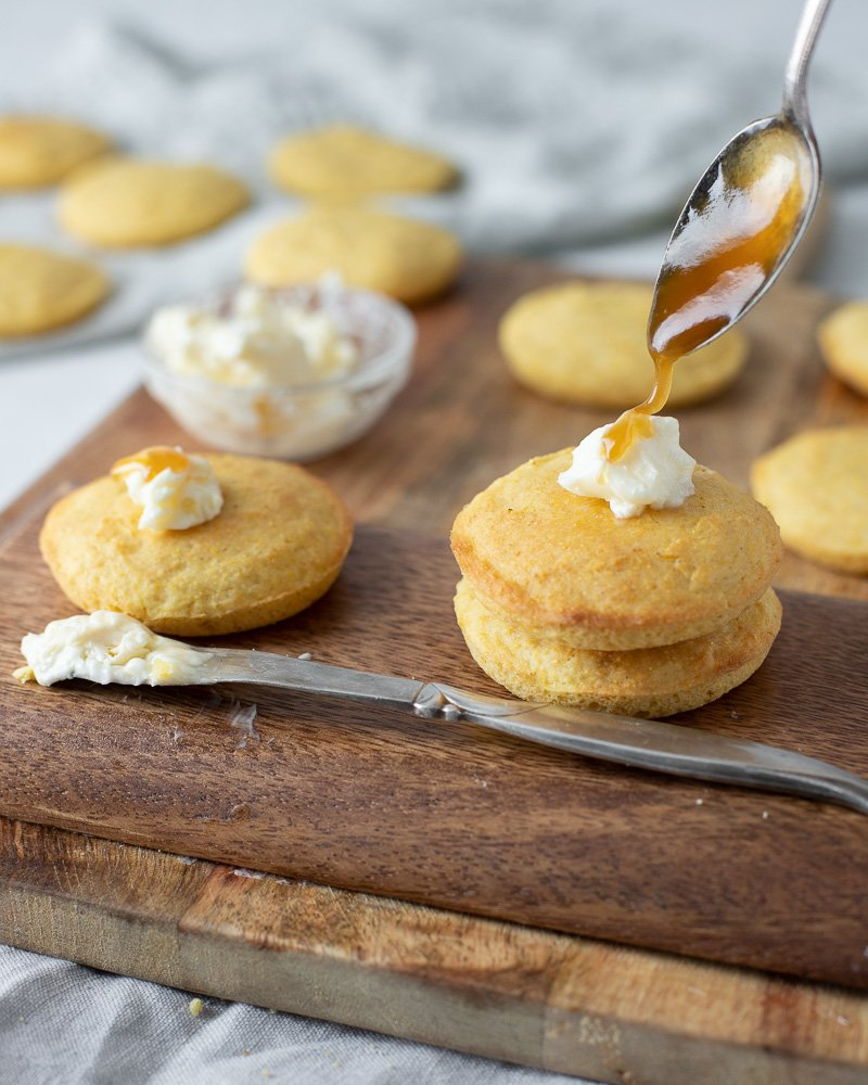 close up of toaster corn muffins with spoon drizzling honey