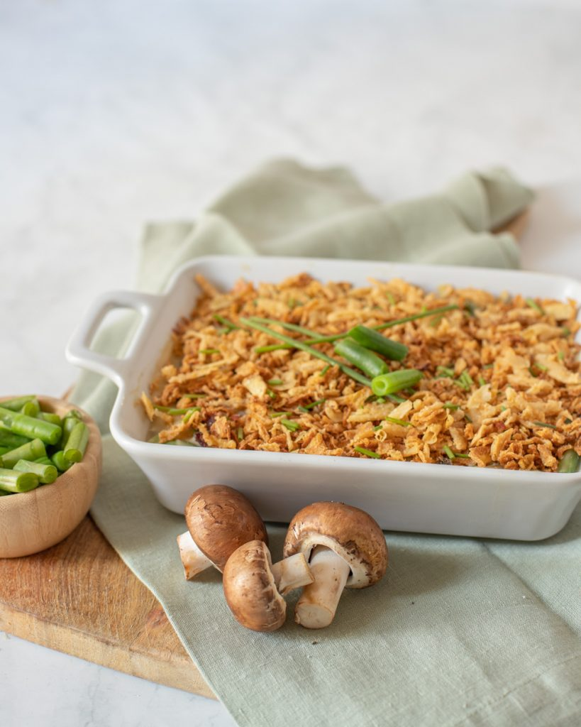 vegan gluten-free green bean casserole in white baking dish with chive topping. Wood board and gray napkin underneath. whole crimini mushrooms in front and small wood bowl with green beans on left.
