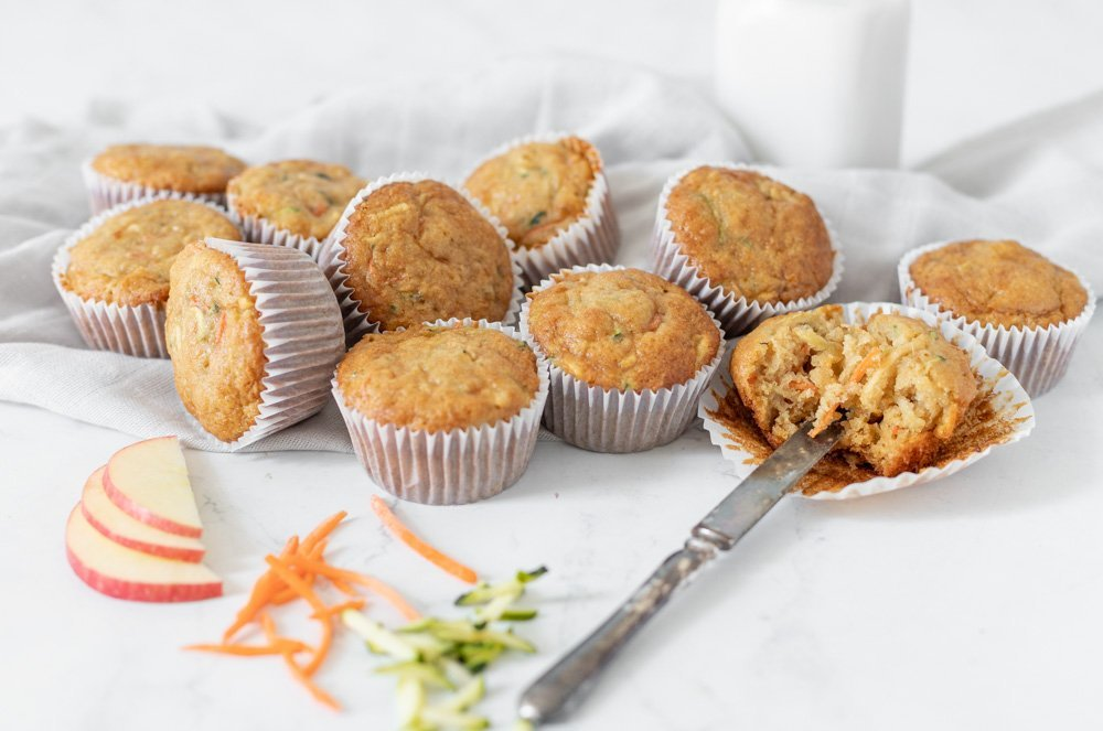 gluten free zucchini carrot apple muffins on gray napkin. On broken open with knife. Shredded carrot and zucchini and sliced apple in front. Milk bottle in back