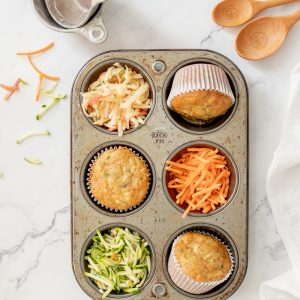 overhead view of muffin tin with gluten free zucchini carrot apple muffins, shredded carrot apple and zucchini. White napkin on right, wood spoons in upper right and metal measuring cups in upper left