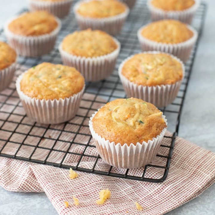 gluten free zucchini carrot apple muffins on wire cooling rack. Red napkin underneath
