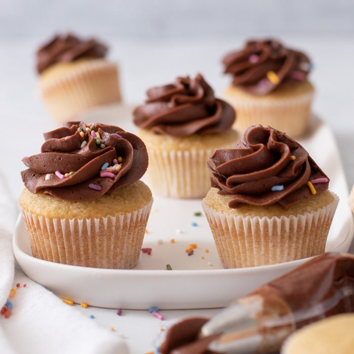 close up of vanilla cupcakes with chocolate buttercream frosting on white platter, Piping bag with frosting in front.