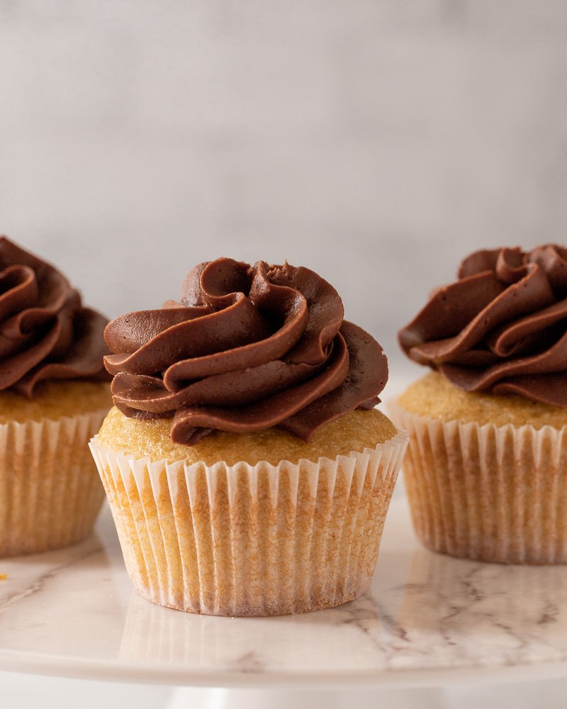 close up of 3 gluten free dairy free cupcakes with chocolate frosting on marble plate, gray background