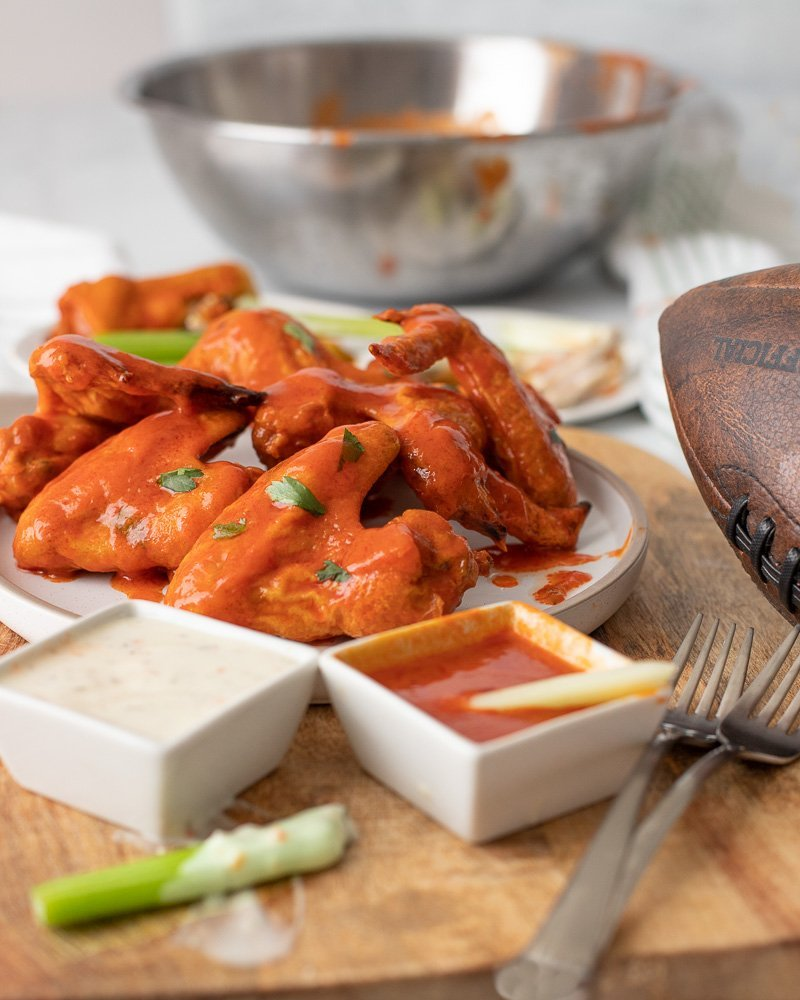 crispy gluten free chicken wings piled on white plate on top of wood board. Forks, celery sticks and small square bowls of ranch dressing and hot sauce in front. Football on right and large metal bowl dripping with buffalo sauce in back.