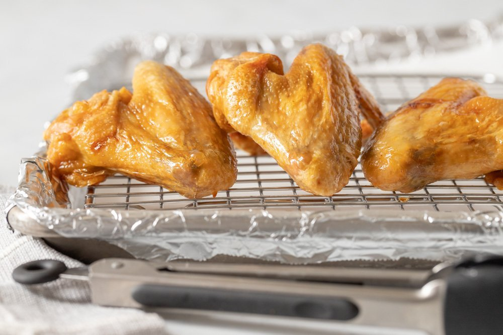 close up of baked gluten free chicken wings on wire rack with tongs in front