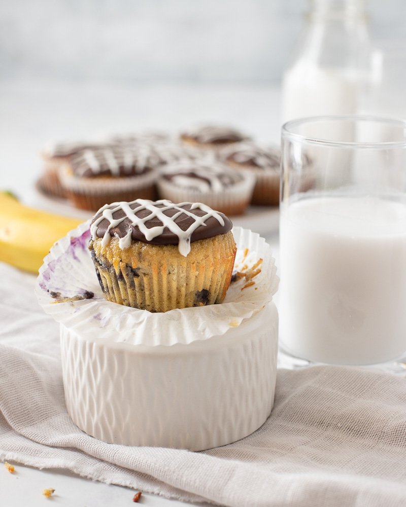 healthy banana cupcake (gluten-free) on upside down white bowl. Banana and plate of cupcakes on plate in background