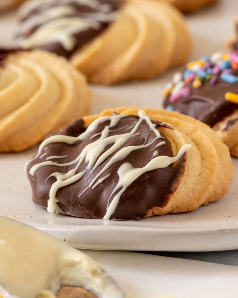 Close up of gluten-free butter cookie dipped in dark and white chocolate.