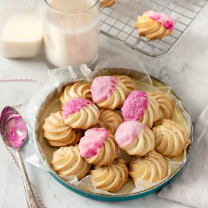 tin with gluten-free butter cookies topped with coarse sugar and pink icing. Spoon with icing on left, milk glass and bottle and wire rack with cookies in background.