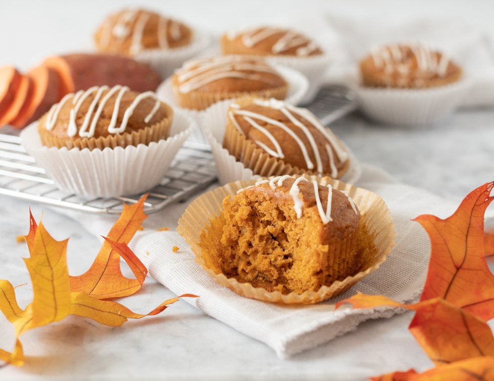 gluten-free sweet potato muffin with drzzle of white icing, bite taken out of. Wire rack in back with muffins and sliced sweet potato/ Gray napkin underneath, autumn leaves in front