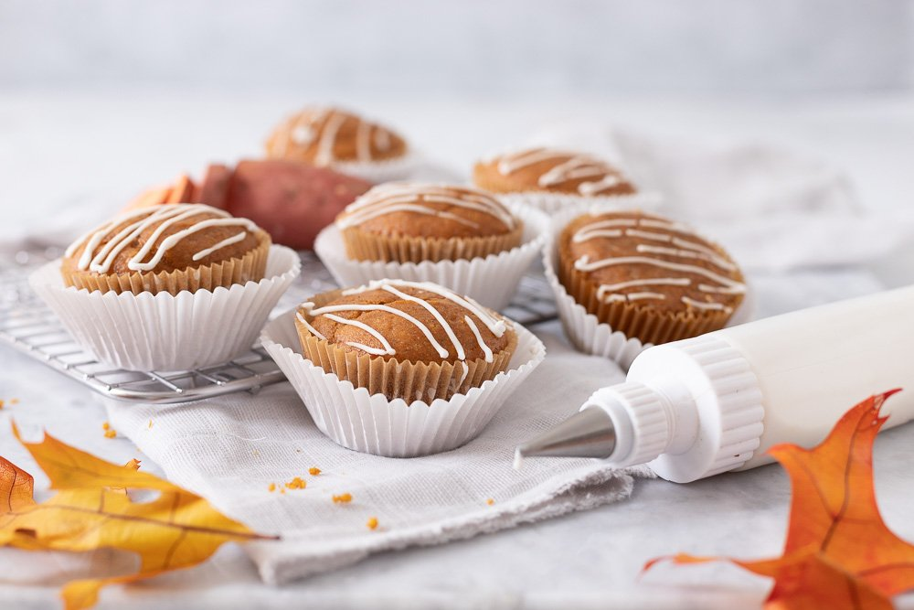 gluten free sweet potato muffins with white icing drizzle on gray napkin and wire cooling rack. squeeze bottle in front dripping icing and autumn leave in front.