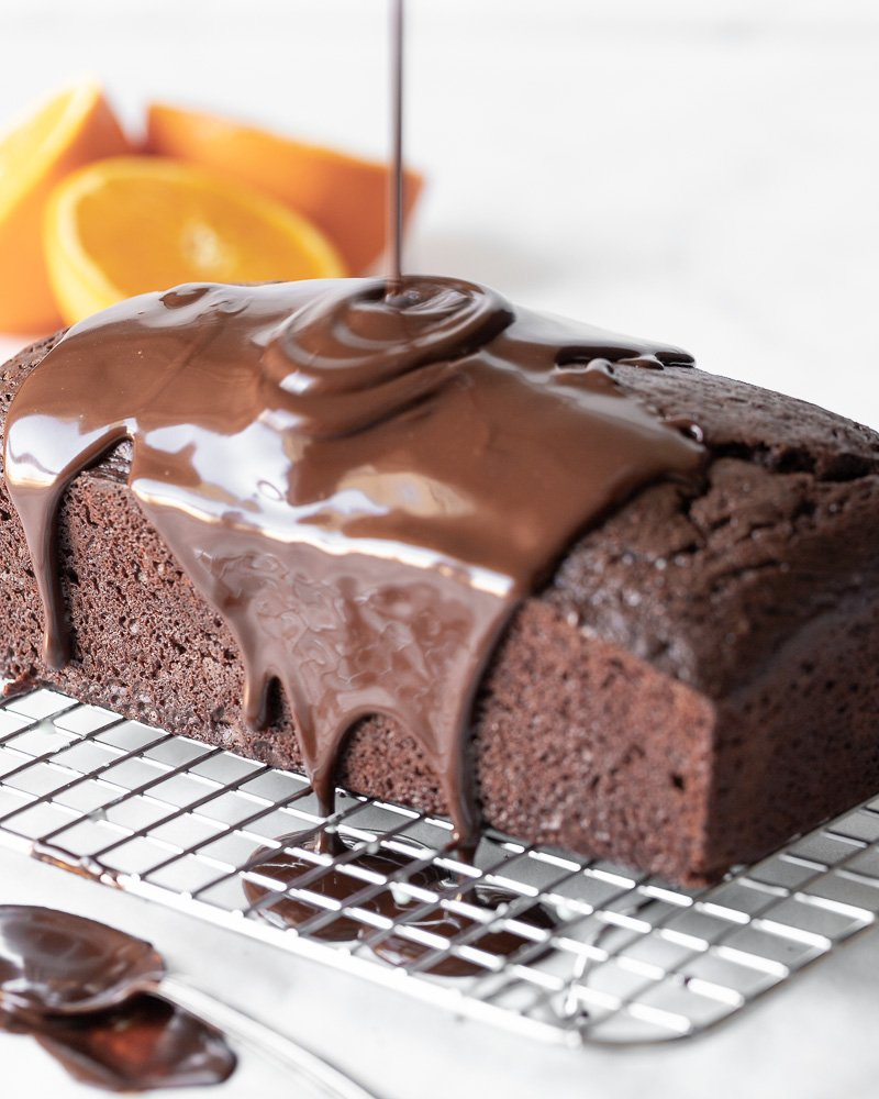 gluten and dairy free chocolate loaf cake on wire rack with chocolate ganache being poured on and dripping down sides of cake. Orange slices in back.