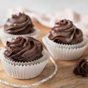 3 gluten-free cupcakes with vegan chocolate cream cheese frosting on wood board. Piping bag with frosting on right.
