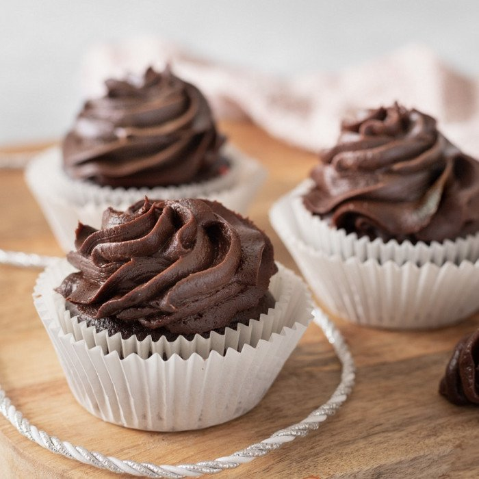 3 gluten-free cupcakes with chocolate frosting on wood board. Piping bag with frosting on right.