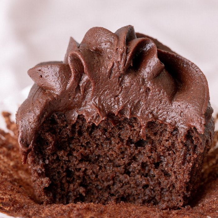 close up of gluten free dairy free chocolate cupcake with vegan chocolate cream cheese frosting. Bite taken out
