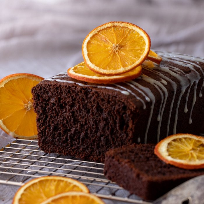 gluten free chocolate orange loaf cake with white chocolate ganache on wire rack. Slice of cake on right. Dried orange slices on top and left. gray background