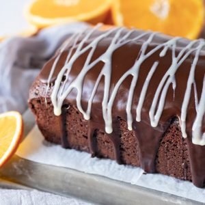 gluten and dairy free chocolate loaf cake with chocolate ganache coating and white choclate ganache drizzle. Orange slices on left and in back.