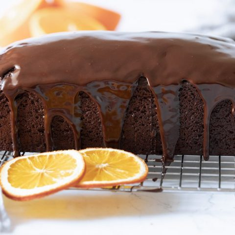 gluten free chocolate loaf cake on wire rack with ganache dripping down sides. Orange slices in front and back.