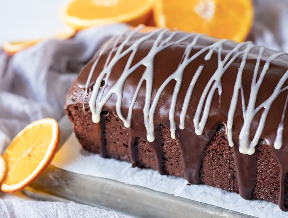 gluten and dairy free chocolate loaf cake with chocolate ganache coating and white chocolate ganache drizzle. Orange slices on left and in back.